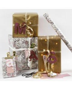 Geschenkverpackungen in Rosa und Gold mit Buchstaben