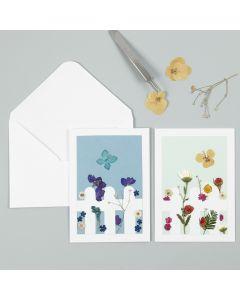 Grußkarte, verziert mit Trockenblumen und Zaun