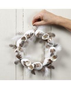 Dekorativer Kranz aus Plastikeiern, geschmückt mit Perlhuhnfedern