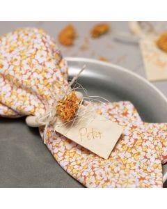 Aus Patchwork-Stoff genähte Servietten, geschmückt mit Serviettenring, Anhänger und Trockenblumen