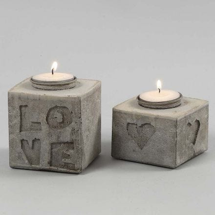 Aus Betonmasse gegossener Kerzenhalter mit Relief aus Buchstaben und Zahlen