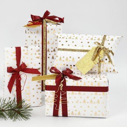 Geschenkverpackungen in Gold und Weiß, verziert mit Band und Drahtfiguren