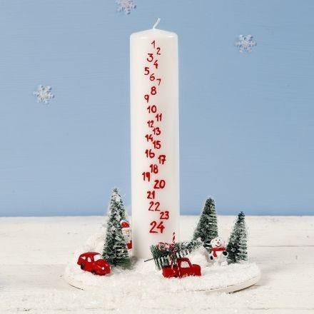 Deko aus Adventskerze und weihnachtlicher Miniaturwelt