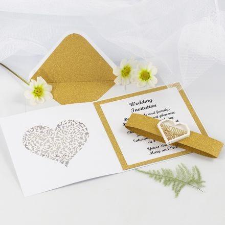 Hochzeitseinladung, gebastelt aus goldenem Glitzerpapier, verziert mit herzförmigen Shaker Stickern