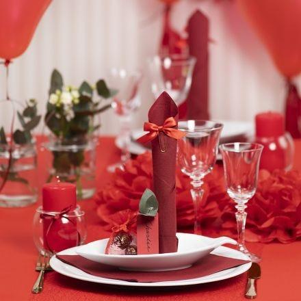 Tischdeko in Rot mit Papierblumen, Luftballons, zum Turm gefaltete Serviette und Platzkarten