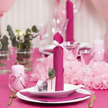 Tischdeko in Pink mit Papierblumen, Luftballons, zum Turm gefaltete Serviette und Platzkarten