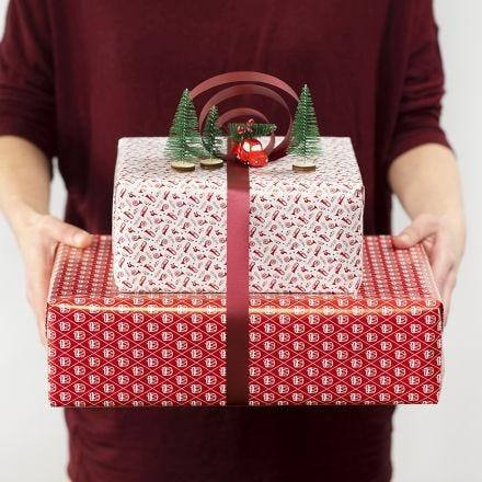 Geschenkverpackung mit dekorativer Schleife und kleinen Figuren
