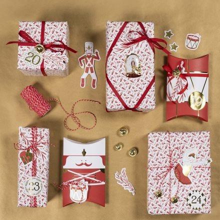 Weihnachtliche Geschenkverpackung, verziert mit Glöckchen, Stickern und Stanzmotiven