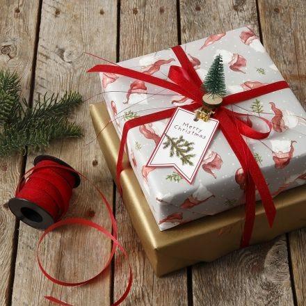 Weihnachtspaket mit Mini-Weihnachtsbaum auf einer Wäscheklammer