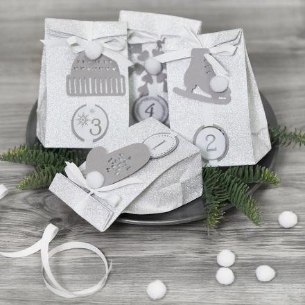 Adventkalender-Geschenke, verziert mit Wintermotiven aus Karton und Pompons