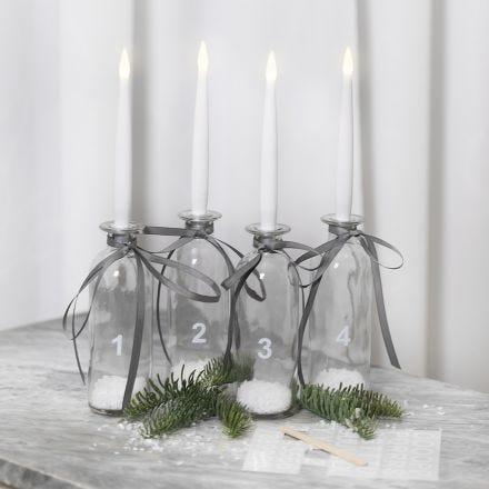 Advent-Deko aus Glasflaschen und LED-Kerzen, geschmückt mit Stickern und Schneeflocken