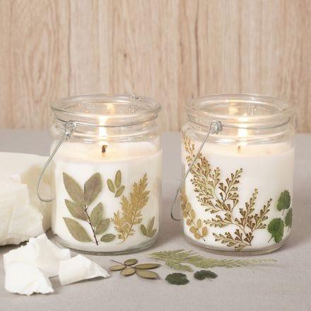 Rapswachs-Kerze in einer mit Trockenblumen verzierten Glaslaterne