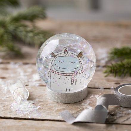 Schneekugel mit einer Zeichnung im Glitterregen