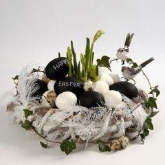 Ein Kranz aus Zweigen, mit Federn und beschrifteten Eiern