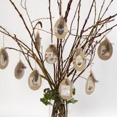 Flache Papp-Eier mit aufgeklebten Motiven und Perlhuhn-Federn