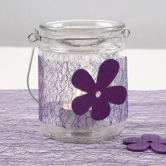 Ein Teelichthalter aus Glas, verziert mit lilafarbener Bordüre aus Netzgewebe und Filzblume