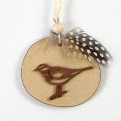 Vogel auf einer Holzscheibe mit Perlhuhnfeder und Flachsband geschmückt