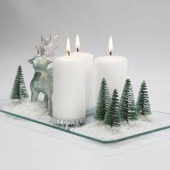 Weihnachtliche Schneelandschaft mit Kerzen, Tannenbäumen und Rentieren auf einer Glasplatte