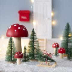 Der kleine Kobold stellt einen Weihnachtsbaum vor sein Haus
