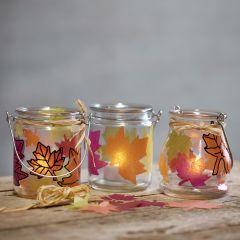 Kleine Glaslaternen, verziert mit Herbstlaub