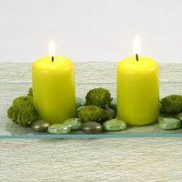 Limettengrüne Stumpenkerzen und Glas-Deko-Steine auf Glasteller