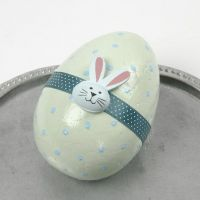 Ein in Pastell bemaltes Ei mit Bordüre und Holz-Sticker