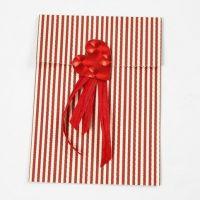 Ein Herz aus Folie mit Geschenkband auf einer Vivi Gade Design Papiertüte.