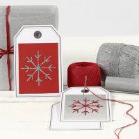 Eine Postkarte mit gestickter Schneeflocke als Geschenkanhänger