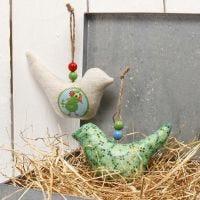 Ein Stoffvogel zum Aufhängen, verziert mit Decoupage Papier und Perlen