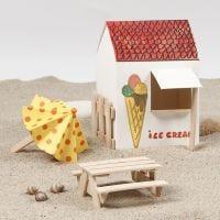 Sonnenschirm und Picknick-Tisch mit zwei Sitzbänken, gebastelt aus Eisstielen