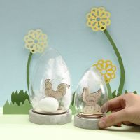 Glasglocke mit Ei, weißer Feder und Osterfiguren aus Holz zur eigenen Gestaltung