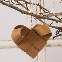 Aus Lederpapier-Streifen geflochtenes Herz als hängende Weihnachtsdekoration
