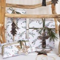 Weihnachtliche Geschenkverpackung und Deko - mit grünen Zweigen bedrucktes Papier, dekoriert mit echten Zweigen und Anhängern aus Baumrinde