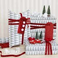 Geschenkverpackungen für Weihnachten, dekoriert mit Pompons und kleinen Figuren