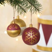Hölzerne Christbaumkugeln, verziert mit Bastelfarbe und Plus Color-Markern