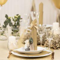 Tischdeko in Gold mit Papierblumen, Luftballons, zum Turm gefaltete Serviette und Platzkarten
