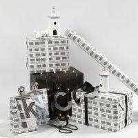 Geschenkverpackungen in Schwarz und Weiß mit Häuschen und Lichterketten