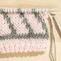 Hier lernen Sie, wie man ein Jacquardmuster mit zwei Farben strickt.