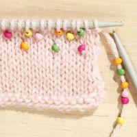 Lernen Sie, wie man kleine Perlen in ein Strickteil einarbeitet.