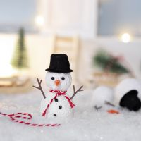 Der kleine Kobold baut einen Schneemann vor seinem Haus
