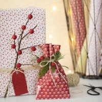 Weihnachtliche Geschenkverpackung mit Naturzweig und Kunstbeeren