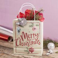 Geschenktüte mit Weihnachtsmotiv, verziert mit Stern, Lametta und Seidenpapier