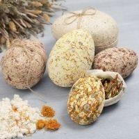 Zweiteilige Pappmaché-Eier, ummantelt mit Pulpe, verziert mit getrockneten Blüten